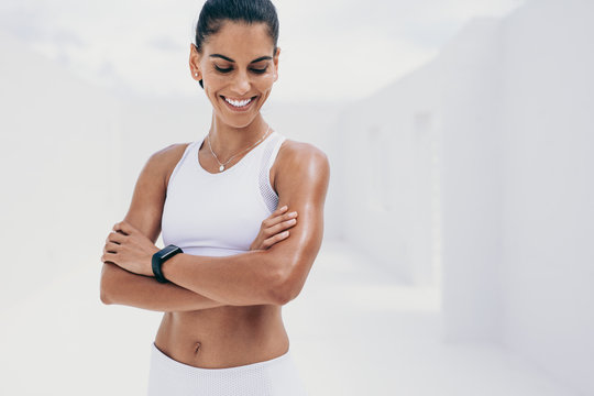 Smiling fitness woman standing with arms crossed