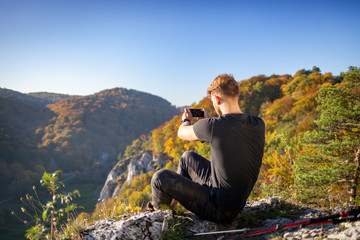 Traveler man after trekking sitting on rock looking at mountain view and making photo