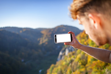 Traveler man looking at mountain view and making landscape photo using smartphone, blank screen copy space