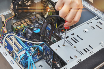 Repairman is installing HDD of desktop computer.