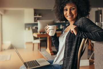 Beautiful woman at home with laptop and having coffee