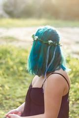 a girl sit on a park with blue hair