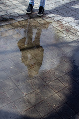 reflection of a young woman on a puddle in the street
