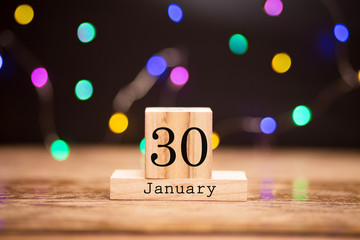 Wooden calendar with black 30 january word at center of dark background with garland bokeh. Winter time, year concept.