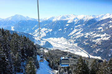 People enjoying skiing on prepared slopes in the Alps on sunny day. Modern comfortable gondola lift in Alpine ski resort. Perfect winter holidays destination for family.