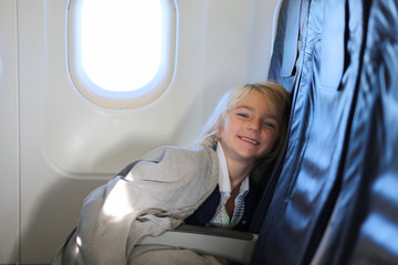 Happy little girl enjoying and relaxing in the airplane. Family traveling by plane to holiday destination. Children friendly airline.