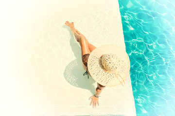 Pretty woman in a hat enjoying a swimming pool