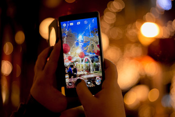 A person captures Christmas decorations on smartphone