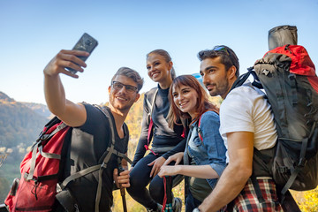 Friends with backpacks making selfie photo together at the peak of mount, travel and tourism concept