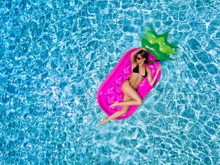 Attraktives Bikini Model entspannt auf einer pinken Luftmatratze über blauem, klarem Pool Wasser im Sommer