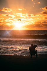 silhouette of a photographer on the beach at sunset