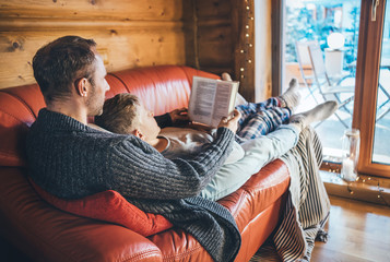 Father and son reading book together lying on the cozy sofa in warm country house. Reading to kids conceptual image.