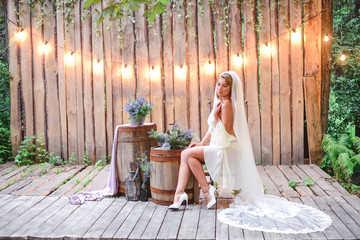 Bride with long veil in wedding boudoir dress seat on chair in wood lavender decor with garland of lights