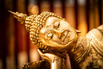 Face of a golden Tuesday Buddha statue.