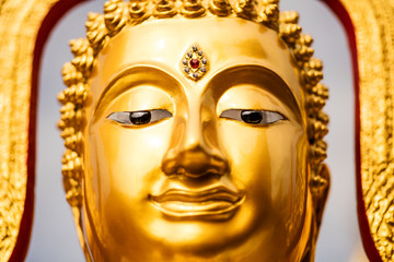 Face of a golden Buddha statue.