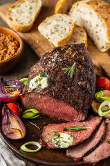Roast beef on cutting board. Wooden background. Copy space.