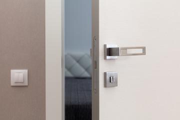 Open white door with metallic handle. The door to the bedroom