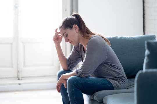 Young woman suffering from depression feeling sad and lonely on sofa at home