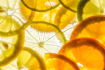 abstract texture of back lit lemon limes and orange fruits slices