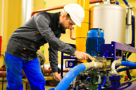 Worker in industrial plant using power oil cleaner