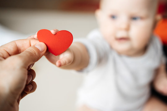 The symbol of a red heart in the hand of a man transmitting it to a child in a small hand in the background.