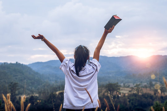 young woman holding bible and lift up hand with light sunset background,christian concept.