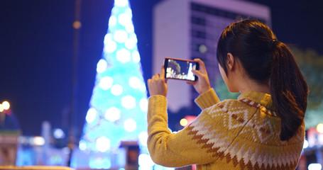 Woman take photo on christmas tree decoration