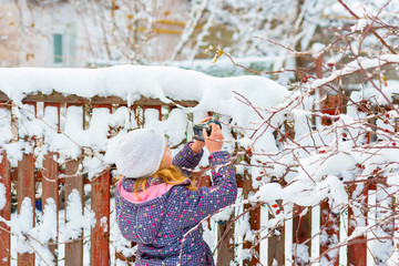 A girl walks in winter with a camera and takes pictures of sights in a snow-covered city.