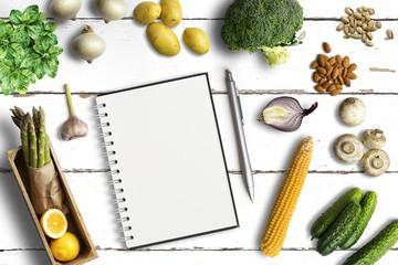 gesunde Lebensmittel und leerer Notizblock auf weißem Untergrund