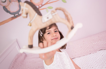 Adorable, cute little girl close-up photo of her looking through her wooden horse toy