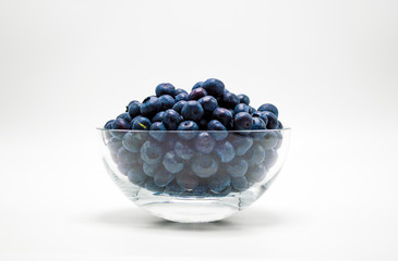 glass bowl full of ripe juicy blueberries isolated on white
