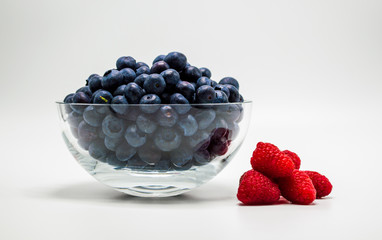 glass bowl full of ripe juicy blueberries next to bright red raspberries isolated on white