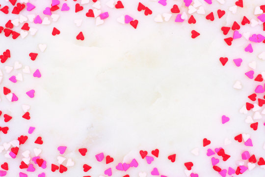 Valentines Day candy heart sprinkles frame over a white marble stone textured background