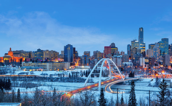 Edmonton Downtown Skyline Just After Sunset in the Winter Showing Alberta Legislature and Walterdale Bridge Over the frozen Saskatchewan River