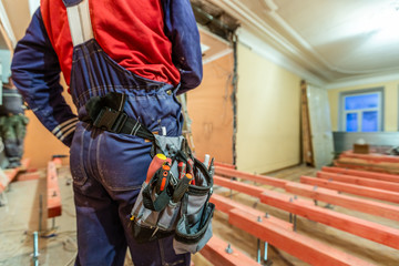 Construction worker with workwear and tool baf with tools on the waist  in apartment is inder construction, remodeling, renovation, overhaul, extension, restoration and reconstruction. Concept of hom