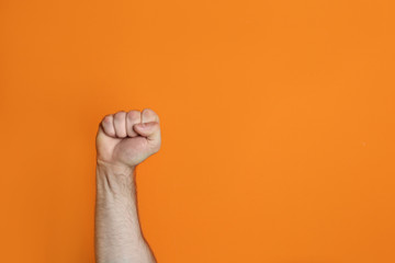 Young man showing clenched fist on color background. Space for text Fototapete