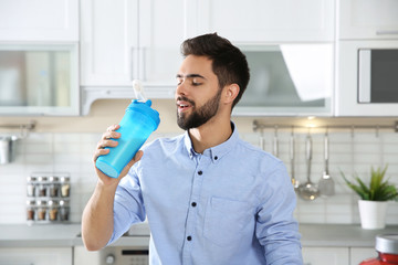 Young man drinking protein shake in kitchen