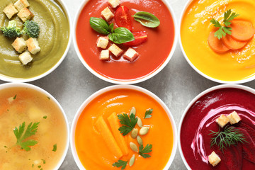Various cream soups in bowls on grey background, top view