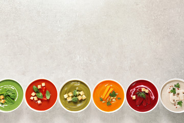 Various cream soups in bowls and space for text on grey background, top view