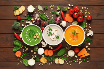 Various cream soups and ingredients on wooden background, flat lay. Healthy food