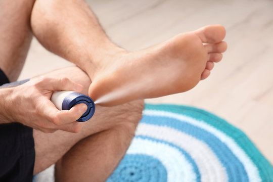 Man using foot deodorant at home, closeup view