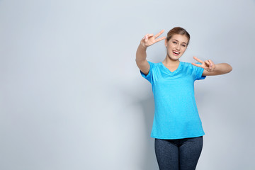 Happy young woman showing victory gesture on color background. Space for text