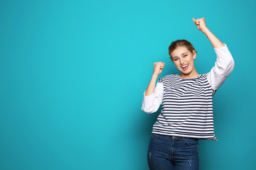 Happy young woman celebrating victory on color background. Space for text
