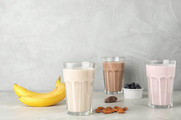 Glasses with different protein shakes and ingredients on table. Space for text