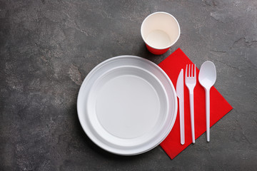 Composition with plastic dishware on grey background, flat lay. Picnic table setting