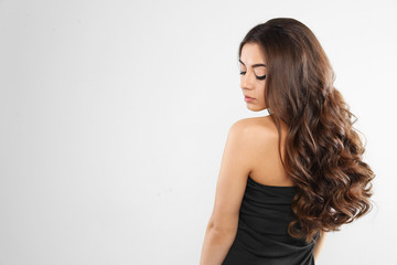 Beautiful woman with shiny wavy hair on white background. Space for text