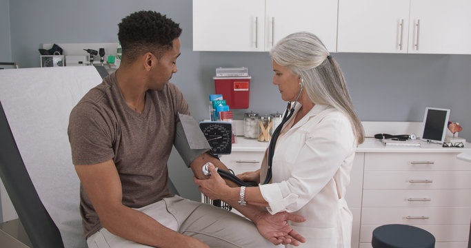 Senior caucasian doctor using stethoscope and gauge to measure patients blood pressure. Young black male seated in medical clinic having his blood pressure measured by mature female doctor
