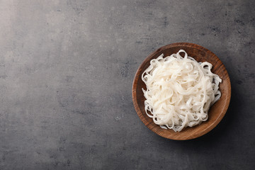 Bowl with rice noodles on grey background, top view. Space for text