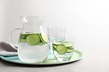 Glasses and jug of fresh cucumber water on tray. Space for text