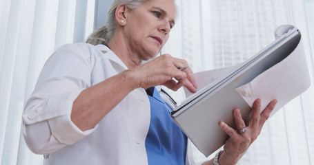 Elderly female caucasian doctor taking notes on patient on clipboard. Senior medical physician writing notes on patients file inside office